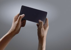 Hands playing game on smartphone on dark background