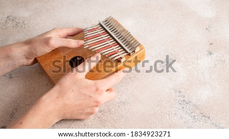 Photo of  Hands playing Kalimba. Kalimba or mbira is an African musical instrument. Traditional to the Shona people, Zimbabwe