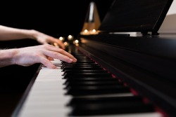 Hands playing the piano keyboard closeup and candle light bokeh background. Male pianist learning to play the piano instrument and beautiful music. Reading sheet music