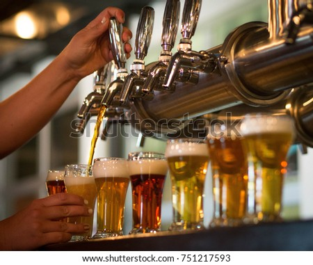 Hands pouring a flight of beer samples #751217593