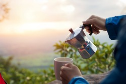 Hands pouring coffee from Mocha Pot, coffee and nature