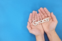 Hands praying for grace from God in blue background top view.