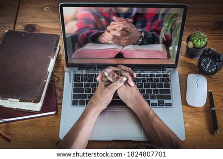 Hands praying on computer laptop, Online church for cell group, Home church during quarantine coronavirus Covid-19, Religion concept