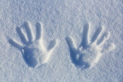 Hands prints on the cold white snow with a winter sunny day. Widescreen frame backdrop.
