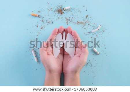 Hands protect lungs from cigarette on light blue background. Stop smoking. World No Tobacco Day concept. Copy space for advertisers.