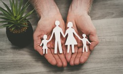 Hands protecting a family; symbol of life insurance