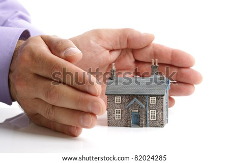 Hands protecting a model house, real estate or insurance concept