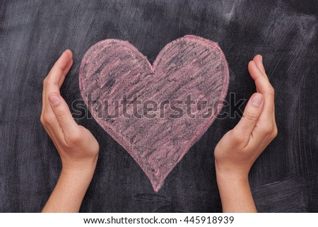Hands protecting a pink heart shape on black chalkboard background. Close up. #445918939