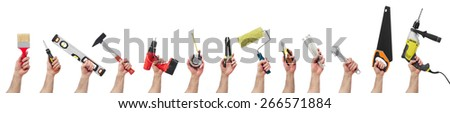 Hands raised holding different tools #266571884