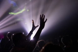 Hands raised in excitement and praise at contemporary church concert and bright lights