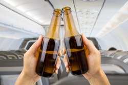 hands raised toasting with beer inside of an airplane a bachelor party trip