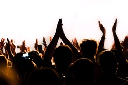Hands raised up in a colorful stage lights of night club show