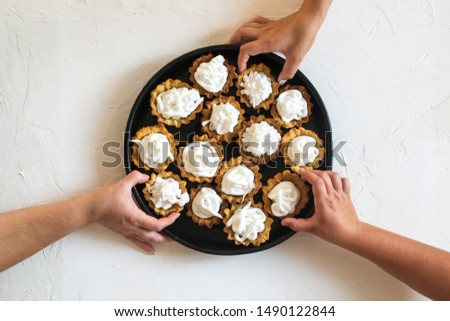 Hands reaching for cakes. Homemade baking.