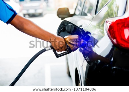 hands refilling the car with fuel at the gas  station, black car in gas station, refilling the car with fuel at the refuel station, the concept of fuel energy