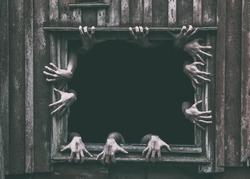 Hands rising out from the old window ancient house, Halloween concept.