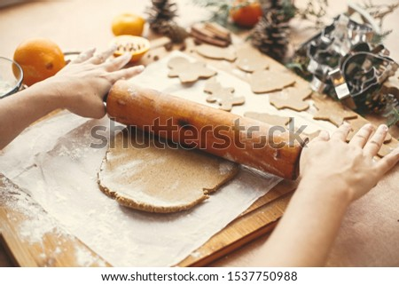 Hands rolling raw dough with wooden rolling pin on background of metal cutters, anise, ginger, cinnamon, pine cones, fir branches on rustic table.Making christmas gingerbread cookies. #1537750988