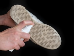 Hands sanitizes shoe sole against coronavirus. Disinfectant spray on the sole of shoe isolated on black background