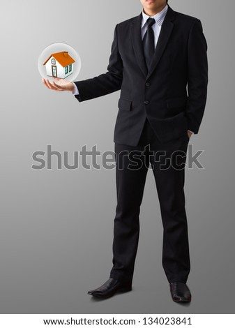 hands saving small home in glass ball