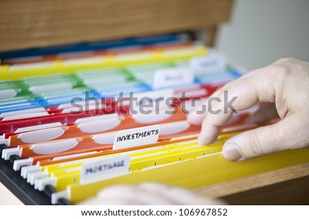 Hands searching through file folders with personal finance documents