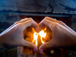 Hands shaped in a heart against a fireplace background