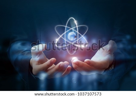 Hands shows the atom on a dark blurred background.