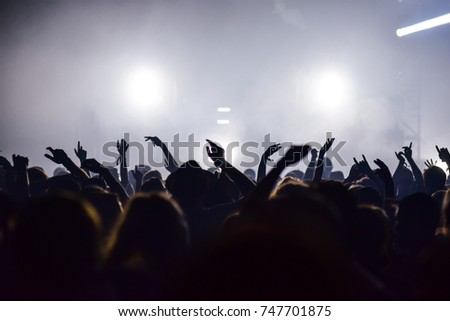 Hands silhouette in the air on concert, party in summer music festival. Entertainment, group dance, DJ play music, people have fun. #747701875