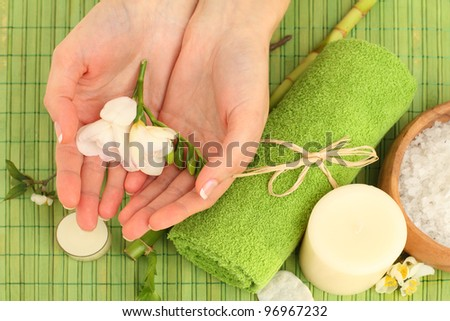 Hands spa - green background with flowers and bamboo