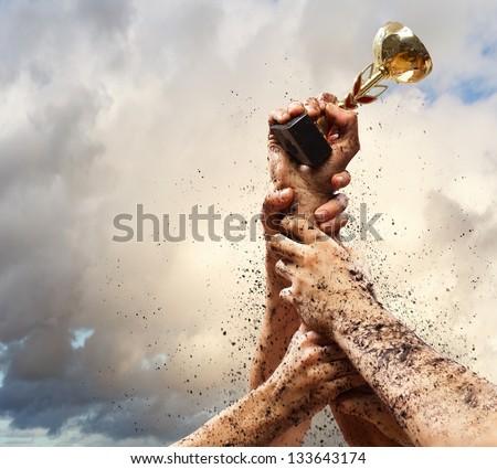Hands squeeze the cup winner against lightning dark sky.