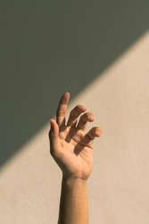 Hands standing straight on the wall exposed to the sun.
