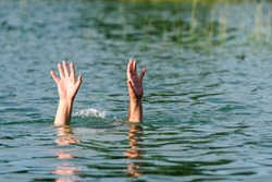 Hands stick out of the water to represent a drowning person