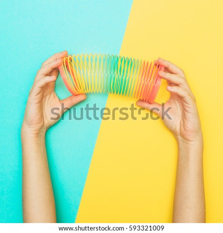 hands stretched rainbow spiral. toy from childhood. retro style. minimalism and flat lay