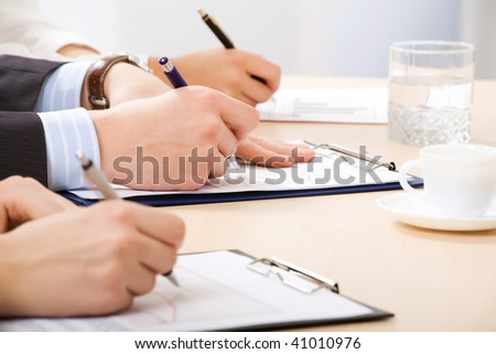 Hands taking notes