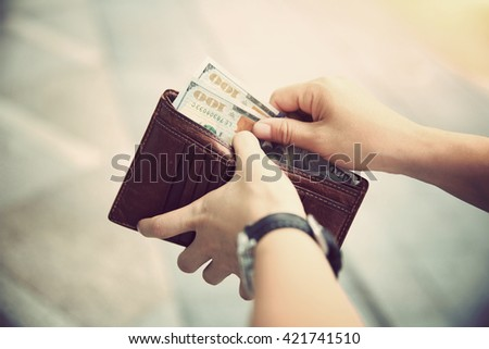 hands taking out money from...