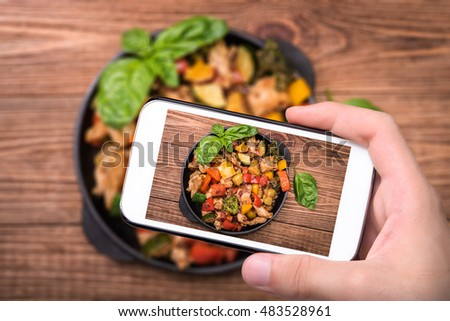 Hands taking photo mexican chicken stir fry with smartphone.