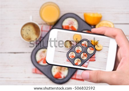 Hands taking photo muffin tin baked eggs with smartphone.