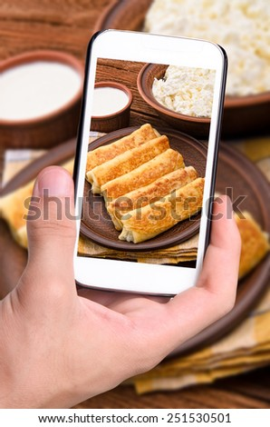 Hands taking photo pancakes with cottage cheese with smartphone.