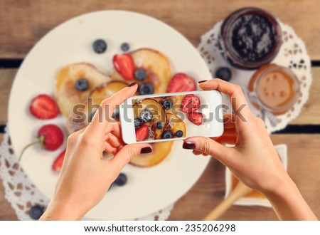 Hands taking picture of pancakes