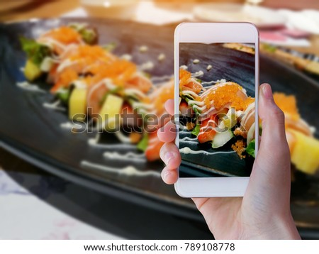 Hands taking picture of sushi japan food with smartphone.