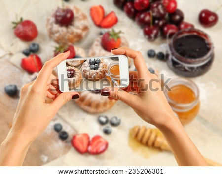 Hands taking picture of sweet cakes