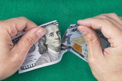 Hands tearing money. Hands tearing one hundred dollar note. Green Blur background. Concept