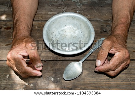 hands the poor old man's and empty bowl on wood background. The concept of hunger or poverty. Selective focus. Poverty in retirement.Homeless.  Alms Stock photo ©
