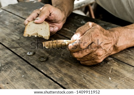 Hands the poor old man's, piece of bread and change, pennies on wood background. The concept of hunger or poverty. Selective focus. Poverty in retirement.Homeless. Сток-фото ©