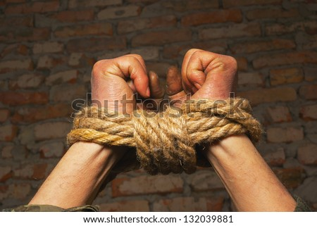Hands tied up with rope against brick wall - stock photo