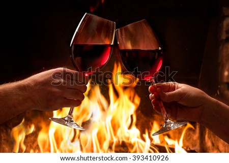 Hands toasting wine glasses in front of lit fireplace