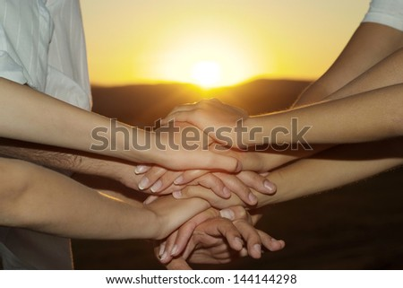 hands together against the sunset
