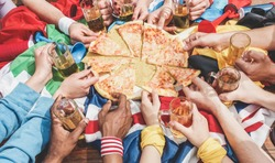 Hands top view of football supporter sharing pizza and drinking half pint beers - Sport fans having fun after game match - Friendship concept with soccer fan enjoying food - Focus on top hands