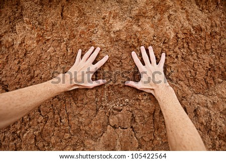 Hands touch the dry clay soil