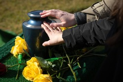 Hands touching a burial urn in a bright outdoor funeral scene, with space for text on the right