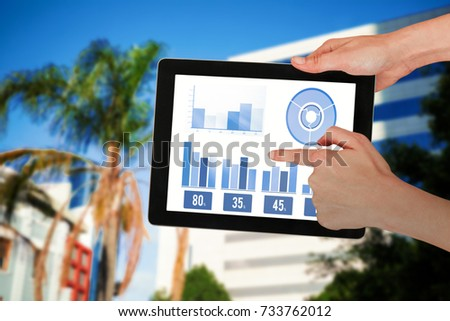 Hands touching digital tablet against white background against tree by glass building #733762012
