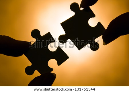hands trying to fit two puzzle pieces together.